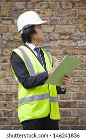 Young male supervisor writing notes at construction site
