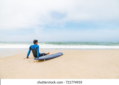 Young male surfer wearing wetsuit, sitting beside his surfboard on beach after morning surfing session.