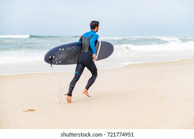 Young male surfer wearing wetsuit, holding surfboard under his arm, running on beach after morning surfing session.