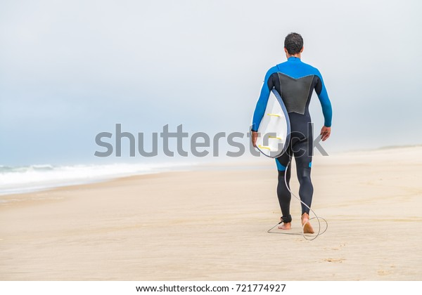 Young male surfer wearing wetsuit, holding surfboard under his arm, walking on beach after morning surfing session.