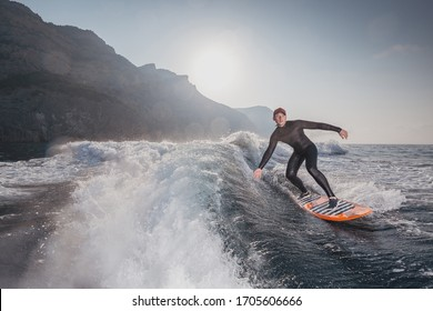 A young male surfer in a wetsuit surfs near the cliffs on the waves in the morning. Professional surfrider training.