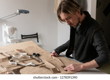 Young male tailor creating clothing pattern while working at workplace