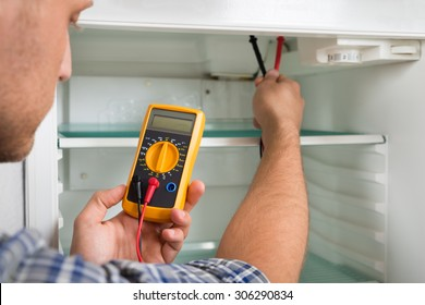 Young Male Technician Checking Fridge With Digital Multimeter