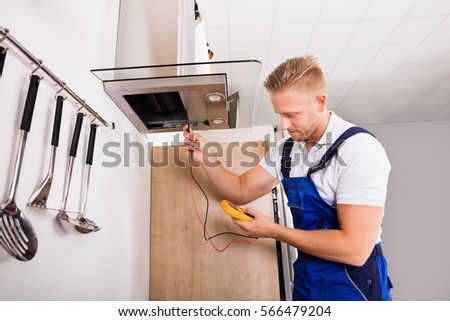Young Male Technician Checking Kitchen Extractor Filter With Digital Multimeter