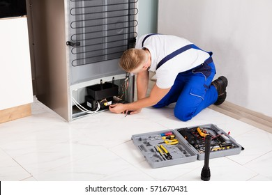Young Male Technician Checking Refrigerator With Screwdriver