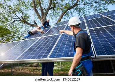 Young male technician with electrical screwdriver standing in front of unfinished high exterior solar panel photo voltaic system pointing at workers connecting panels to high steel platform.