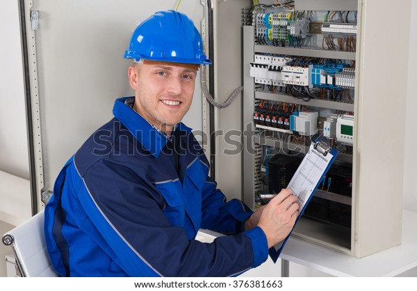 Young Male Technician Holding Clipboard While Examining Fusebox