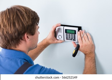 Young Male Technician Installing Security System Using Screwdriver
