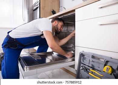 Young Male Technician Repairing Dishwasher In Kitchen