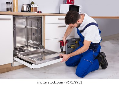 Young Male Technician Repairing Dishwasher In Kitchen