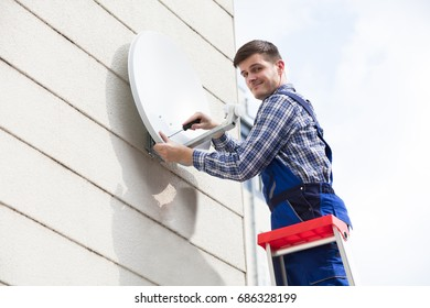 Young Male Technician In Uniform Installing TV Satellite Dish On Wall