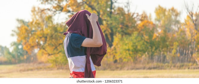 young male teenage hipster put on a sweatshirt sweater outdoors walking in nature field