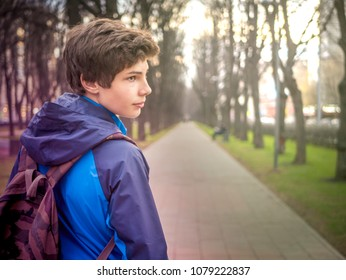 young male teenager schoolboy in the city with backpack