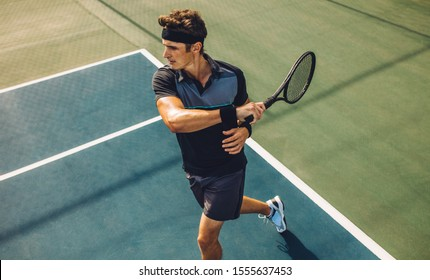 Young male tennis player hitting forehand during practice game on hard court. Pro tennis player playing tennis on court.