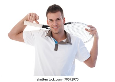 Young male tennis player taking a break, smiling, holding tennis racket.?