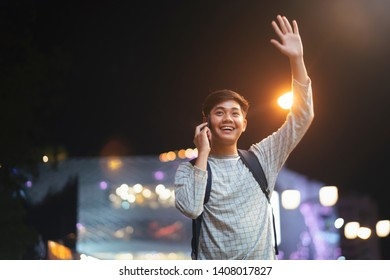 Young male tourist with backpack walking through city street talking the mobilephone and waving hand.  Young man hailing for taxi waiting for transport in city center holding backpack.