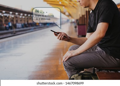 Young male tourist and backpacker using a phone while waiting for a public transportation inside train platform - receiving train arrival push notification notice via apps