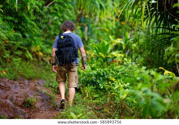 Young male tourist hiking on the famous Kalalau trail along Na Pali coast of the island of Kauai in the state of Hawaii
