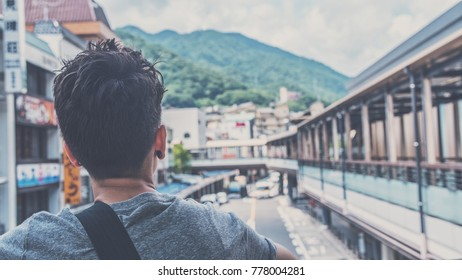 A young male tourist looks out over a quaint town in Japan.