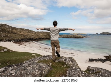 Young male tourist with open arms admiring a desert white beach with blue sea in the Isle of Lewis, Outer Hebrides, Scotland (UK).