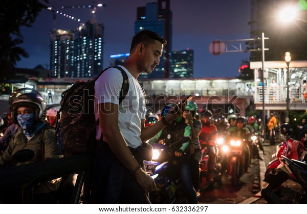 Young male tourist using the mobile phone while walking on a crowded street with people on scooters in Jakarta at night