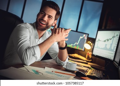 Young male trader at office work concept sitting looking aside cheerful