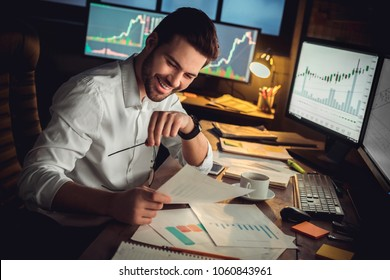 Young male trader at office work concept sitting looking at charts happy