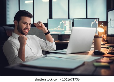 Young male trader at office work concept sitting looking at laptop happy