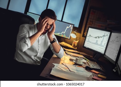 Young male trader at office work concept sitting having headache