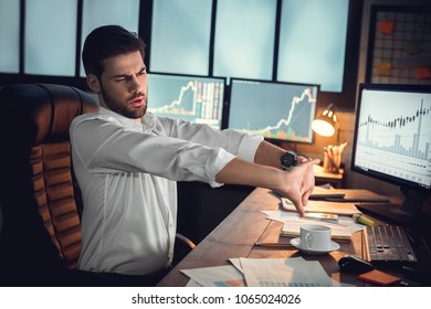 Young male trader at office work concept sitting stretching