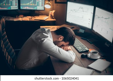 Young male trader at office work concept lying tired