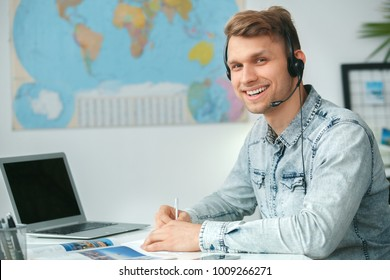Young male travel agent consultant in tour agency wearing headset