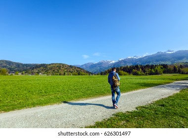 Young male traveler carrying backpack walking on walk path in green nature in spring landscape of European alps on sunny day