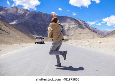 Young male traveler miss and is late for the car in rural area.