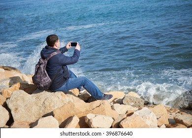 Young male traveler sitting on the rocks and enjoy the views of the sea and nature in Varna Bulgaria, man doing landscape photos on your phone