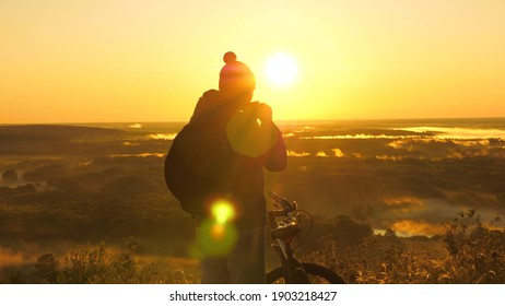 A young male traveler stands on edge of a mountain drinking tea enjoying nature at sunrise. A free tourist travels with a bicycle in nature and drinks tea in sun. Cyclist is resting. Sports lifestyle.