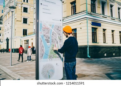 Young male traveler using modern smart board with map and useful information for tourists, caucasian hipster guy searching train on electronic device on street with wifi connection and touchscreen