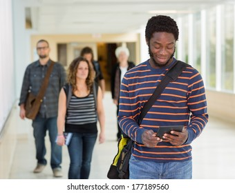 Young male university student using digital tablet while walking down university corridor