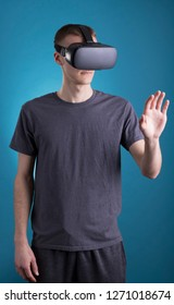 Young male using VR Virtual Reality headset on blue background.
