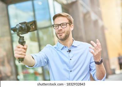 Young male vlogger wearing blue shirt and eyeglasses holding a gimbal with smartphone, talking and gesturing while recording new content for his blog outdoors