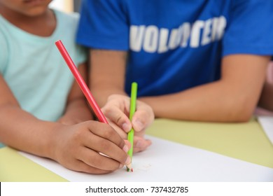 Young male volunteer drawing with little child, closeup. Volunteering abroad concept
