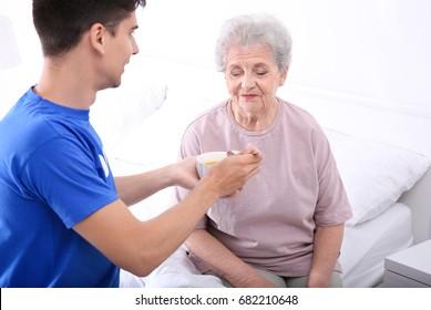 Young male volunteer feeding elderly woman in light room