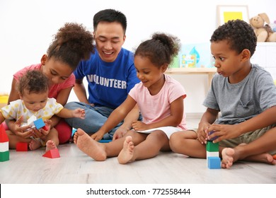 Young male volunteer playing with little children in light room. Volunteering abroad concept
