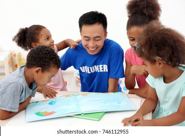 Young male volunteer reading book with little children in light room. Volunteering abroad concept