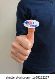 """Young male voter showing an """"I voted"""" sticker on his thumb"""