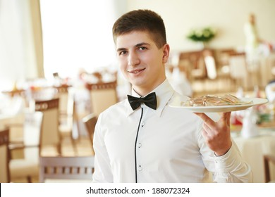 young male waiter with food on tray serving at restaurant