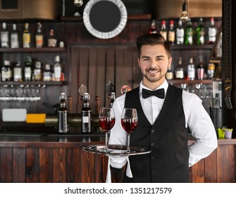 Young male waiter with glasses of wine in restaurant