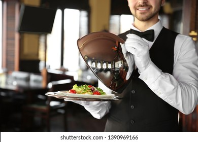 Young male waiter with salad in restaurant