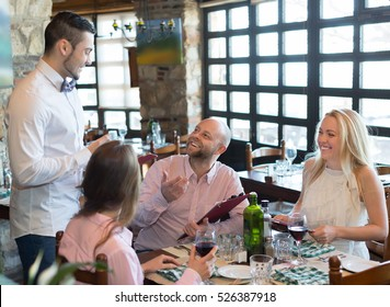 Young male waiter serving cheerful restaurant guests at table. Selective focus