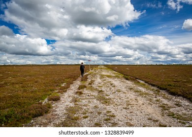 A young male walking alone at a flat highland hiking trail. Scenic landscape view with beautiful clouds.